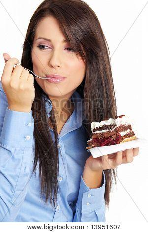 Businesswoman wearing blue shirt eating the cake.