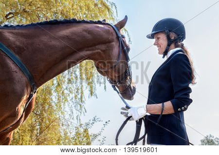 Beautiful Smiling Jockey Girl Stand Next To Her Horse.