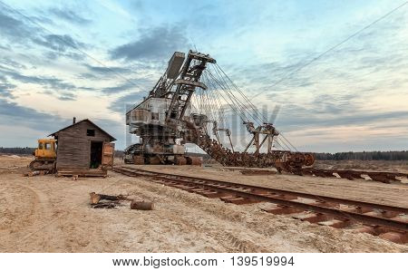Many buckets of giant quarry excavator Equipment for the extraction of sand from the quarry. Dredge near the old railway track