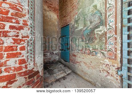 Old wooden blue door to the abandoned bell tower. Partially preserved ancient temple old Russian painting