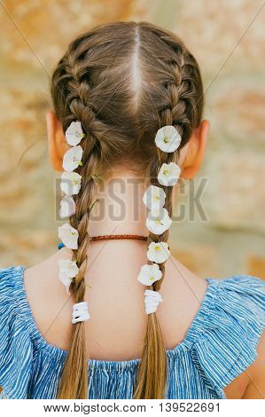 White morning glory flowers in little girl's braids