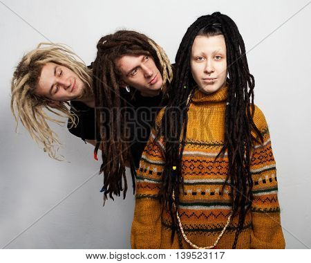 Group portrait of three young freaks with dreadlocks - two boys are looking out behind the girl, white background