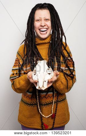 Portrait of a young freaky woman with dreadlocks and piercings holding a scull of an animal