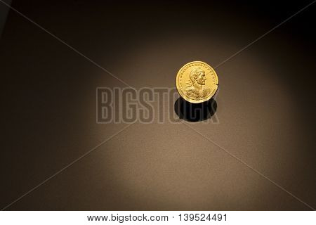 Madrid, Spain - July 11, 2016: Golden Ancient Roman coin on a dark background with spot light circle at National Archeological  Museum of Madrid