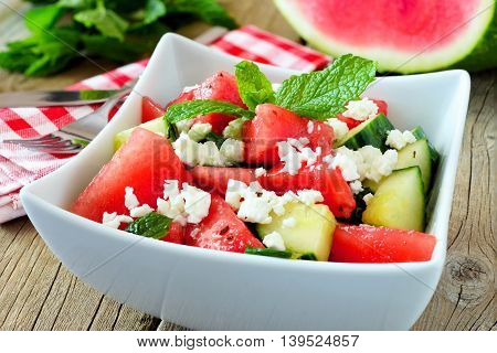 Delicious Watermelon, Cucumber And Feta Cheese Salad In Square Bowl On Wood Background