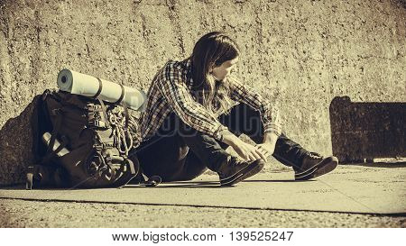 Man Tourist Backpacker Sitting By Grunge Wall Outdoor