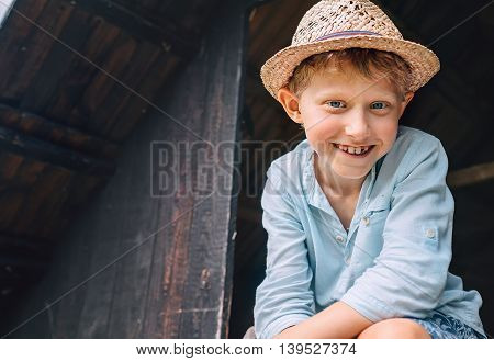 Boy in a straw hat smiles from the shed