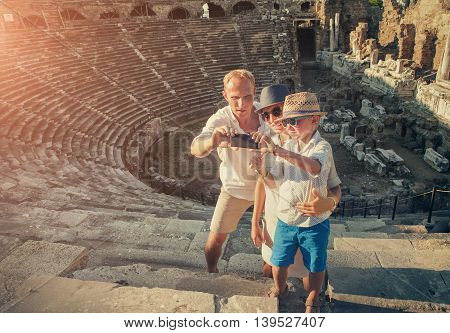 Family takes a vacation selfie photo in the amphitheater