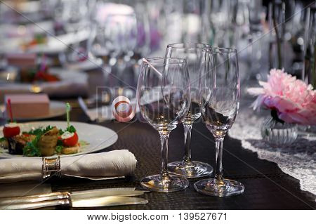 Banquet table covered in natural crocodile skin. Glasses and plates, forks and knives, napkins and buttons for a luxurious celebration in anticipation of guests. Luxury festive table.
