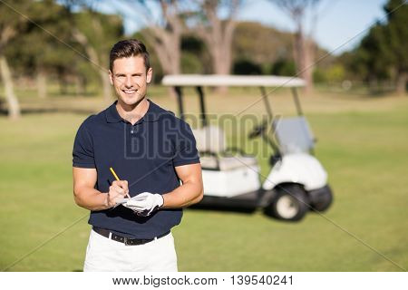 Portrait of smiling golfer writing on score card while standing at golf course