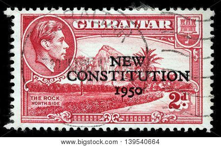 LUGA RUSSIA - JUNE 25 2016: A stamp printed by GIBRALTAR shows image portrait of King George VI against view of Gibraltar Rock North Side circa 1943 (New Constitution Overprint at 1950)