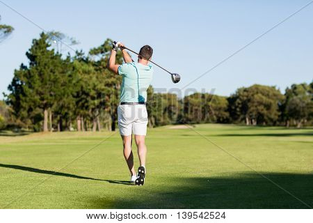 Rear view of young golfer man taking shot while standing on field