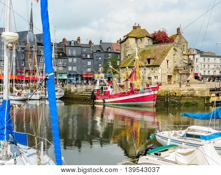HONFLEUR FRANCE - MAY 6, 2014: Old boat The Lieutenancy building or La Lieutenance moored yachts and medieval houses in Old Harbor. Honfleur, Normandy, France