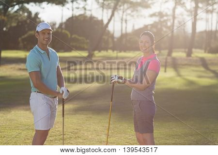 Portrait of smiling golf player couple standing on field
