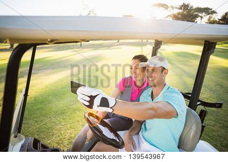 Smiling golfer couple taking selfie while sitting in golf buggy
