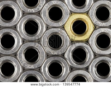 Golden screw nut in steel nuts pattern isolated on black. Abstract background.