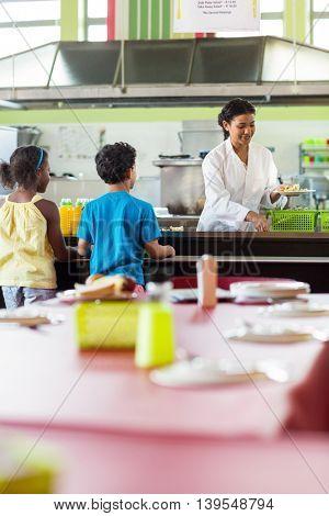 Woman serving food to schoolchildren in canteen