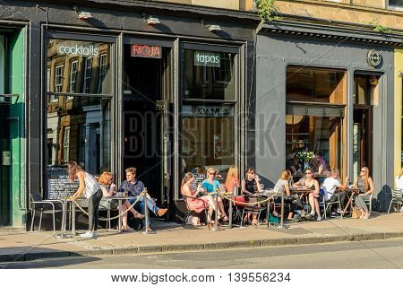 GLASGOW SCOTLAND - JULY 21 2016: People eating outside Rioja restaurant in Argyle Street Finnieston in the west-end of Glasgow.