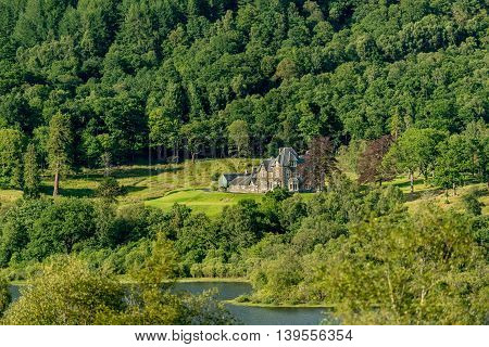 A grand stone house on the banks of Loch Archay Trossachs National Park Stirling District Scotland United Kingdom