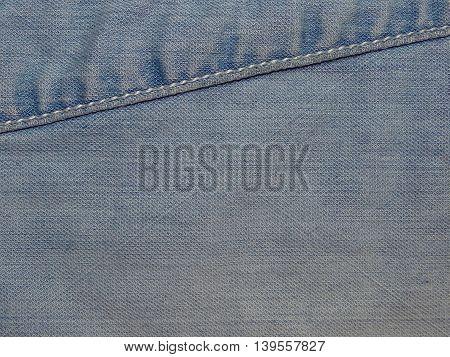 light blue denim fabric sewn into her seams , close up