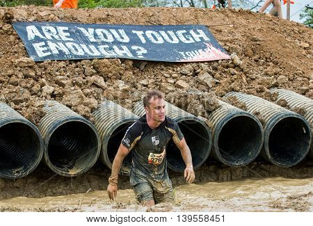 Grantham Leicestershire/UK - May 21, 2016: A participant emerges from the Sewer Rat obstacle at the 2016 Tough Mudder extreme sports charity competition at Belvoir Castle.
