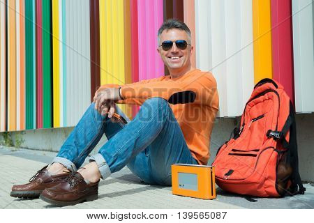 Street fashion. Male outdoor portrait. Happy smiling handsome man sitting near colored urban wall in jeans, orange sweater with backpack and smart phone.