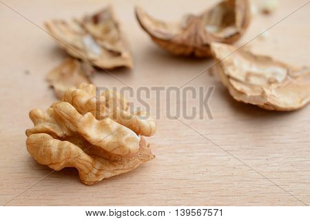 Walnut kernel and cracked nutshell pieces closeup. Shallow depth of field.