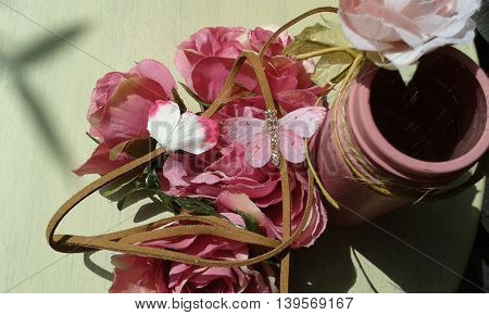 Artificial fabric flowers with butterfly and reworked painted jar