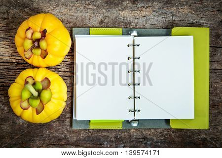Top view. Garcinia cambogia fresh fruit on wood background with book. Garcinia atroviridis is a spice plants and high vitamin C and hydroxy citric acids (HCA) for diet and good health.