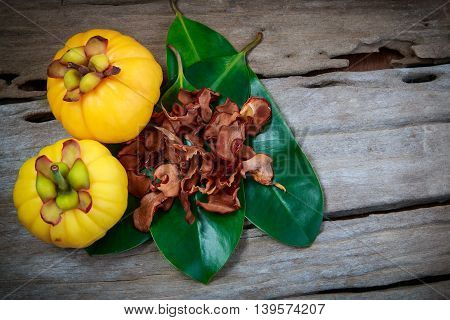 Garcinia Cambogia Fresh Fruit On Wood Background.  Fruit For Diet And Good Health.