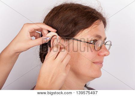 Audiologists hands inserting a hearing aid int an ear of a woman