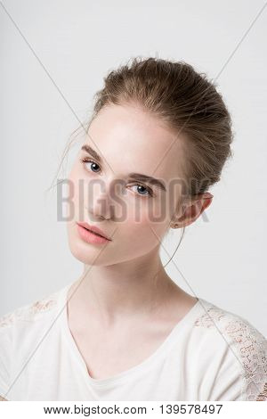 Glamour portrait of beautiful woman model with fresh daily makeup and funny wavy hairstyle. Fashion shiny highlighter on skin, sexy gloss lips make-up and natural eyebrows. gray background