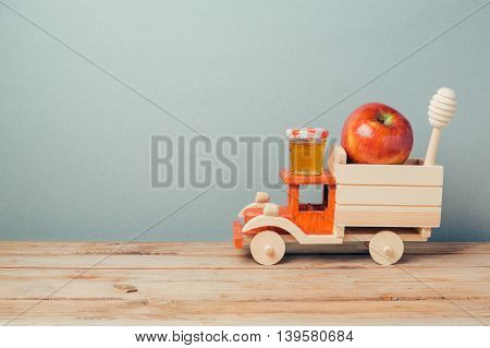 Jewish holiday Rosh Hashana background with toy truck honey and apples on wooden table