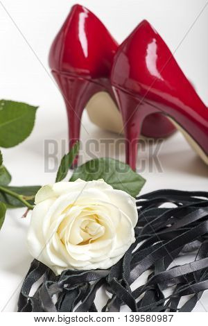 red high heels on white background with whip