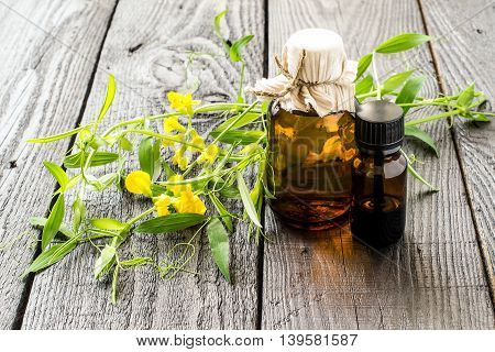 Medicinal plant Lathyrus pratensis or Meadow vetchling and pharmaceutical bottles on a dark wooden table. Used in herbal medicine for livestock feed honey plant. Selective focus
