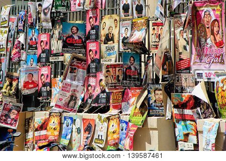 AVIGNON FRANCE - JULY 192014: Plenty of playbills on a wall during famous theatre festival from July 4 to 27 2014 in Avignon south of France.The Avignon Festival is today one of the most important contemporary performing arts events in the world.