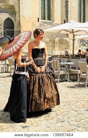AVIGNON FRANCE - JULY 19 2014: Two actresses in historical costumes advertising their performance in front of the Papal Palace during famous theatre festival from July 4 to 27 2014 in Avignon south of France. The Avignon Festival is today one of the most