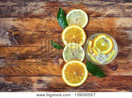 glass homemade lemonade orange lemon stands on old wet rustic wooden table