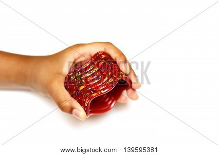 Red Bangles with multi-coloured design in hand on a white background