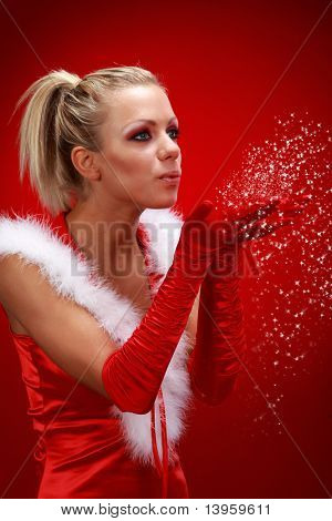 Attracive sexy girl in santa cloth blowing snow from hands.