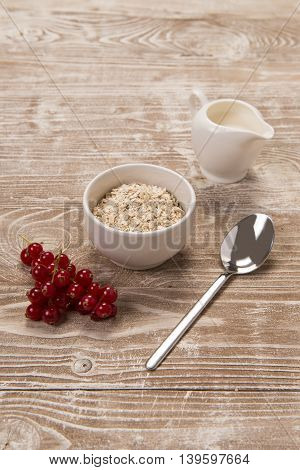 Redcurrants milk and oats in ceramic bowls on whitewashed wood surface