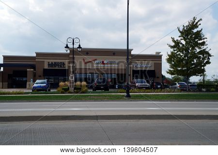 SHOREWOOD, ILLINOIS / UNITED STATES - AUGUST 30, 2015: A strip mall in Shorewood includes a dentist's office, a Verizon Wireless premium retailer, and a Pizza Hut restaurant.