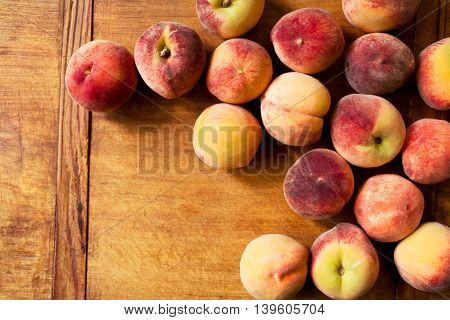 Fresh peaches on a wooden background with copy space on left
