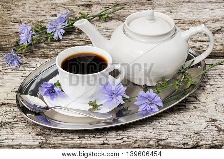 Medicinal plant chicory. The roots of the plants are used as a substitute for coffee. Drink from chicory in a cup and teapot on a metal tray on the old wooden background. Rustic style