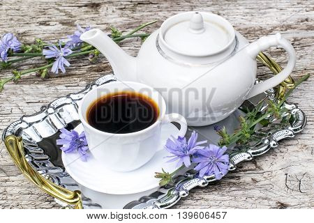 Medicinal plant chicory. The roots of the plants are used as a substitute for coffee. Drink from chicory in a cup and teapot on a metal tray on the old wooden background