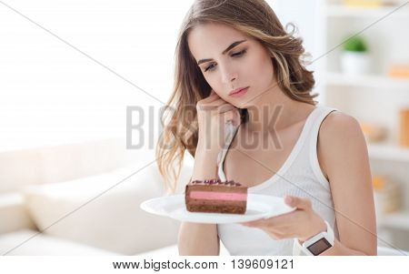 Eat or not . Pleasant thoughtful woman holding plate with cake and looking at it while being involved in thoughts