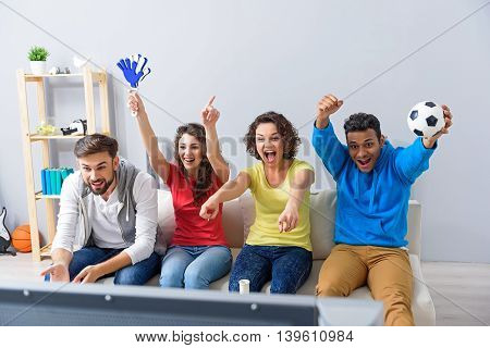 Watching their favourite team win. Group of young football fans cheering on their favourite team, sitting on sofa at home with soccer attributes