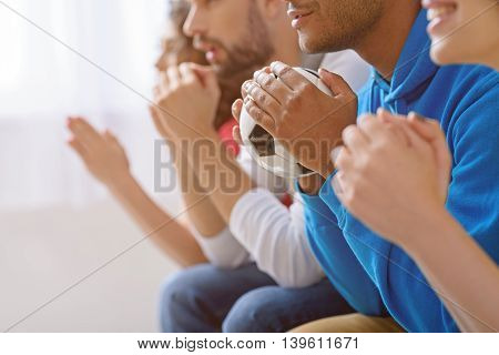 We worring about match very much. Close up of hands of african man holding soccer ball and sitting next to friends, watching sports on TV