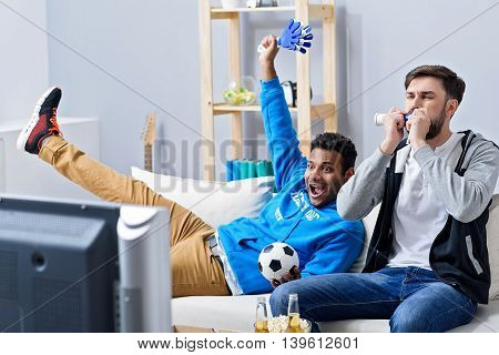 Scored winning goal. Two happy soccer fans sitting on couch and watching sport on TV, celebrating goal