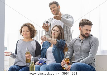 Today is not good day for our team. Group of amazed shocked young friends watching tv and drinking beer on sofa